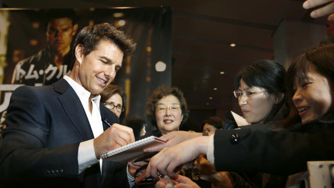 "U.S. actor Tom Cruise signs autographs for fans as he arrives for the Japan premiere of his new movie ""Jack Reacher"" in Tokyo,  Wednesday, Jan. 9, 2013. (AP Photo/Shizuo Kambayashi)"