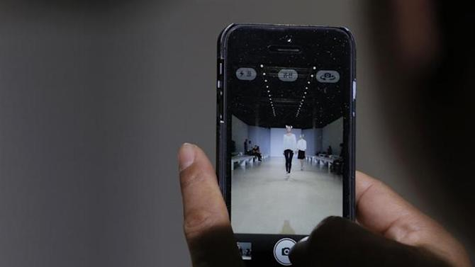 A photographer takes pictures with his iPhone during the rehearsal of South Korean designer Lie Sang Bong's Spring/Summer 2014 women's ready-to-wear collection during Paris Fashion Week October 2, 2013. REUTERS/Gonzalo Fuentes