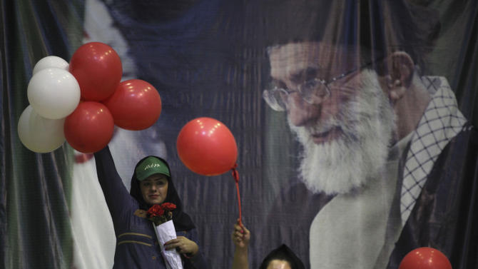 In front of a portrait of Iranian supreme leader Ayatollah Ali Khamenei, supporters of the presidential candidate Ali Akbar Velayati, a conservative former foreign minister, hold up balloons in a campaign rally, two days prior to the election, in Tehran, Iran, Wednesday, June 12, 2013. (AP Photo/Vahid Salemi)