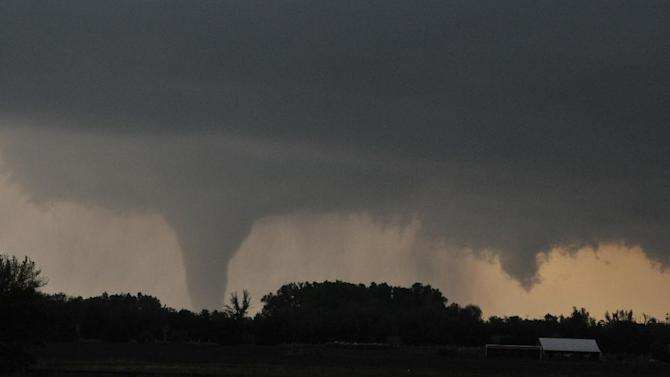 A tornado moves on the ground north of Solomon, Kan., on Saturday evening, April 14, 2012, with I-70 seen in the foreground. (AP Photo/The Hutchinson News, Sandra J. Milburn)