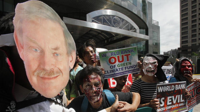 Protesters, dressed in their Halloween costumes and makeup, display placards as they picket the World Bank office Thursday Oct.27, 2011 where visiting World Bank President Robert Zoellick is holding a news conference at suburban Mandaluyong, east of Manila, Philippines. Zoellick welcomed a deal clinched by European leaders to address their two-year debt crisis, saying it may have helped avert the spread of the financial turmoil to emerging markets that provide half of global economic growth. (AP Photo/Bullit Marquez)