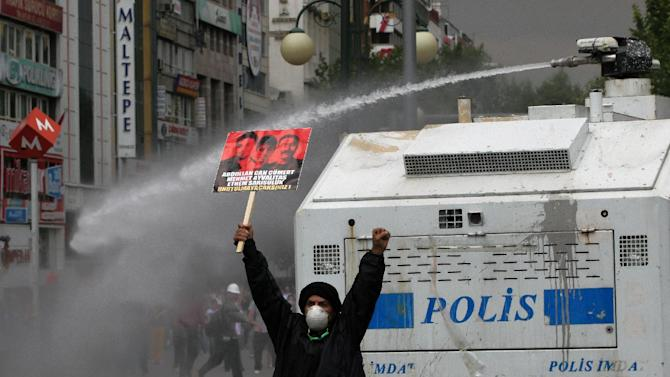 A protester holds up a banner with photos of three victims killed during protests and shouts anti-government slogans as Turkish riot police spray water cannon at demonstrators who remained defiant after authorities evicted activists from an Istanbul park, making clear they are taking a hardline against attempts to rekindle protests that have shaken the country, in city's main Kizilay Square in Ankara, Turkey, Sunday, June 16, 2013.(AP Photo/Burhan Ozbilici)