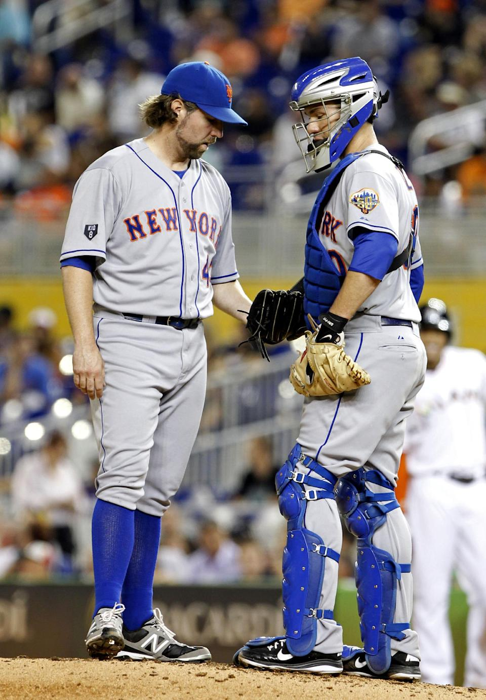 New York Mets' R.A. Dickey, left, talks to catcher Josh Thole after Miami Marlins' Giancarlo Stanton hit a single in the sixth inning of a baseball game in Miami, Tuesday, Oct. 2, 2012. (AP Photo/Alan Diaz)