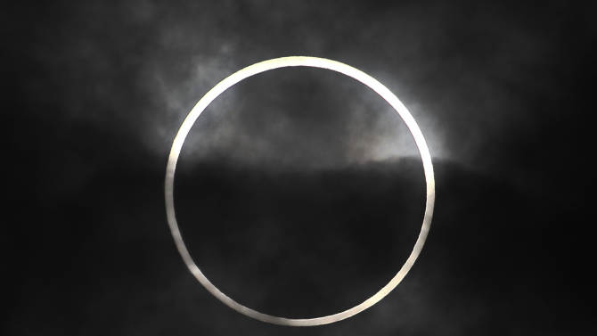 """An annular solar eclipse in seen from Machida, on the outskirts of Tokyo, Monday, May 21, 2012. Millions across Asia are watching as a rare """"ring of fire"""" eclipse is crossing their skies. The annular solar eclipse, in which the moon passes in front of the sun leaving only a golden ring around its edges, was visible to wide areas across the continent Monday morning. (AP Photo/Itsuo Inouye)"""