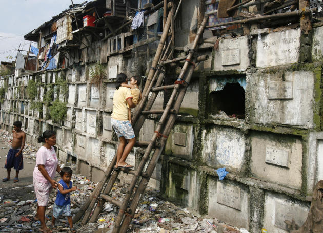 Residents climb into their houses atop gravestones inside a cemetery in Manila