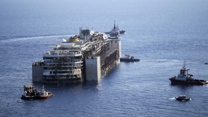 Tugboats drag the cruise liner Costa Concordia as they leave Giglio Island