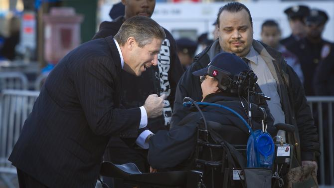 President of the Patrolmen's Benevolent Association Patrick Lynch talks to a man in a wheelchair as he arrives for slain NYPD officer Rafael Ramos' wake at Christ Tabernacle Church in the Queens borough of New York