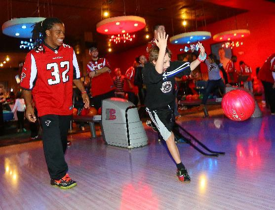 Atlanta Falcons running back Jacquizz Rodgers bowls a game with Ben Pacheco, 10, while Falcons players and UnitedHealthcare of Georgia treat children from the Make-A-Wish Foundation and their families to a night of bowling Tuesday, Dec. 17, 2013, in Lawrenceville, Ga