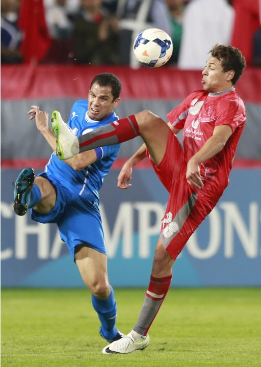 Msakni of Qatar's Lekhwiya fights for the ball with Juliano of Bahrain's Al-Hidd during their AFC Champions League match in Doha
