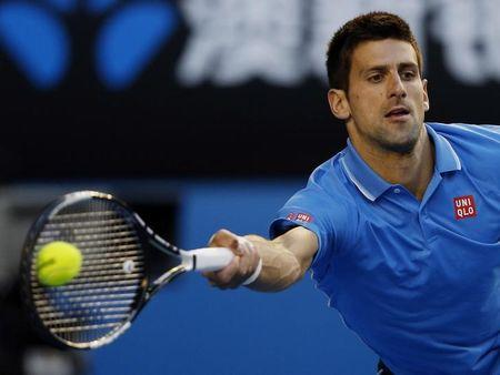 Djokovic of Serbia reaches to hit a return to Wawrinka of Switzerland during their men's singles semi-final match at the Australian Open 2015 tennis tournament in Melbourne