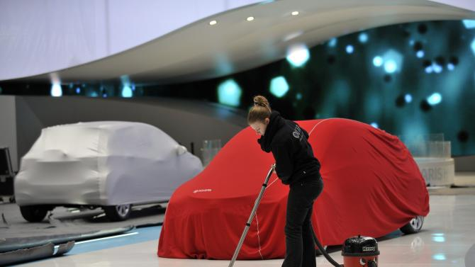 In this picture taken March 3, 2012 a representative of the Toyota booth  cleans the floor next to a car during the last preparations prior to the opening of the press preview days at the 82nd Geneva International Motor Show in Geneva, Switzerland. he Motor Show will open its gates to the public from the  8th to the 18th of March presenting more than 260 exhibitors and more than 180 world and European premieres. (AP Photo/Keystone/Martial Trezzini)