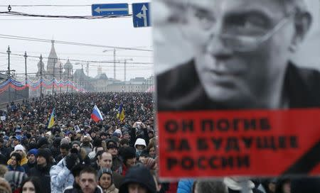 A man holds a poster of Kremlin critic Nemtsov during a march to commemorate him in central Moscow