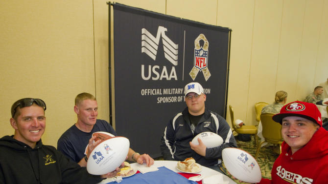 In this photo provided by IMG Consulting, Wounded United States Army soldiers Michael Haydon, left, Timothy Adams, left center, Jonathon Carpenter, right center, and Michael Cagle, far right, all members of the Warrior Transition Battalion at Schofield Barracks enjoy a lunch Thursday, Jan. 24, 2013, in Honolulu. Six National League Football players later joined the soldiers to sign autographs and to learn about the soldier's sacrifices they made for their country at the USAA NFL sponsored event.  (Eugene Tanner/AP Images for USAA. IMG Consulting