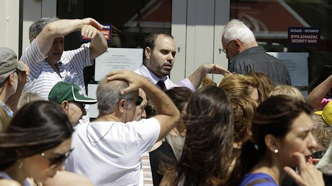People wait to enter a bank for limited services as an employee of the branch tries to serve them in Athens, Friday, July 3, 2015.  Currency restrictions are in place to staunch a possible run on the banks, in the run-up to Greece's critical Europe bailout referendum on Sunday.  (AP Photo/Thanassis Stavrakis)