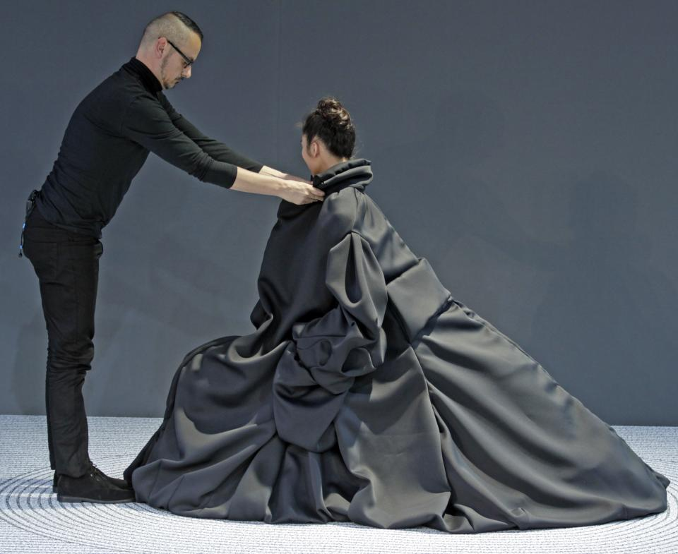 Dutch fashion designer Viktor Horsting, adjusts the creation worn by a model, as part of Viktor and Rolf 's Haute Couture Fall-Winter 2013-2014 collection, presented Wednesday, July 3, 2013 in Paris.(AP Photo/Remy de la Mauviniere)