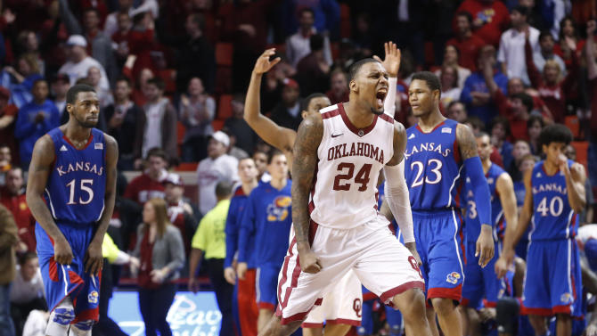 Oklahoma forward Romero Osby (24) reacts in front of Kansas' Elijah Johnson (15), Ben McLemore (23) and Kevin Young (40) at the end of an NCAA college basketball game in Norman, Okla., Saturday, Feb. 9, 2013. Oklahoma won 72-66. (AP Photo/Sue Ogrocki)
