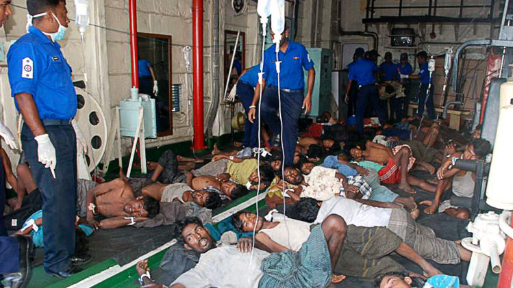 In this picture taken on Sunday, Feb. 17, 2013 and released by Sri Lankan Navy, Myanmar nationals rescued off Sri Lanka's eastern coast on Saturday lie on the floor at a hospital in Galle, Sri Lanka. The navy said it has rescued 32 Myanmar nationals whose wooden vessel began sinking while making a perilous journey to Australia. The group comprising 31 adult males and a boy had been at sea without food for 21 days when the navy rescued them after being informed by a local fishing boat. (AP Photo/Sri Lanka Navy) EDITORIAL USE ONLY