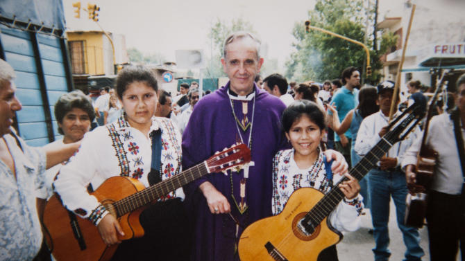 "In this April 2000 photo courtesy of the Espinola family, Buenos Aires' Archbishop Jorge Mario Bergoglio poses for photo with Angela Espinola, 12, left, and her sister Eliza, 9, during an Easter procession organized by the Virgin of Caacupe church in the Villa 21-24 slum in Buenos Aires, Argentina. For more than a billion Catholics worldwide, he's Pope Francis. For Argentina's poorest citizens, who crowd into the many so-called ""misery villages"" that surround the capital, he's proudly known as one of their own, a true ""slum pope."" (AP Photo/Courtesy of the Espinola family)"