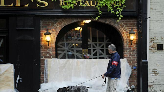 An unidentified local resident walks his dog past a taped and barricaded abd sandbagged restaurant entrance in Old Town Alexandria, Va., Sunday, Aug. 28, 2011, the morning after the passage of Hurricane Irene. The storm did not produce the flooding anticipated in the area. (AP Photo/Cliff Owen)