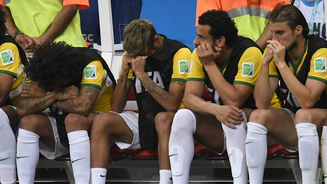 (L-R) Brazil's defender Marcelo, injured forward Neymar, forward Fred and defender Henrique react on the bench at the end of the third place play-off match between Brazil and Netherlands on July 12, 2014