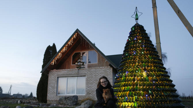 Goda Valukonyte poses by the bottle Christmas tree in the Agariniu village, Lazdijai district, some 176 kilometers (110 miles) from Vilnius, Lithuania, Saturday, Dec. 28, 2013. Lithuanian policeman Dalius Valukonis says he spent three years and hundreds of hours of his free time to create the tree using bottles he got from local restaurants, bars, family and friends. (AP Photo/Mindaugas Kulbis)