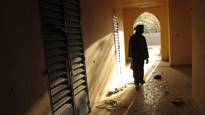 In this Wednesday, Feb. 6, 2013 photo, neighborhood resident Mohamed Alassane walks through the Ministry of Finance's Regional Audit Department in Timbuktu, Mali, a site used by al Qaida-linked Islamists for more than a year. In the building, also used to hold European hostages, the AP found a more than 10-page letter signed by Abdelmalek Droukdel, the senior commander appointed by Osama bin Laden to run al-Qaida's branch in Africa. The confidential letter from the terror leader spelled out the terror network's blueprint for conquering this desert nation.(AP Photo/Rukmini Callimachi)