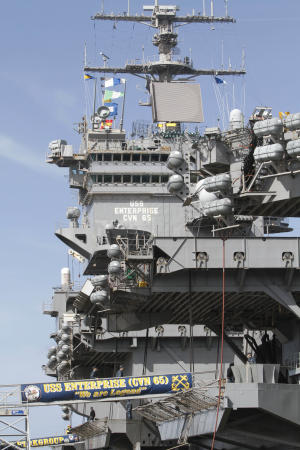 In this March 8, 2012 photo, sailors move supplies and equipment as they prepare for the final deployment of the nuclear aircraft carrier USS Enterprise at the Norfolk Naval Station in Norfolk, Va. The ship's storied 50-year history includes action in several wars, a prominent role in the Cuban missile crisis and serving as a spotter ship for John Glenn's orbit of the Earth. (AP Photo/Steve Helber)