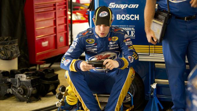 Brad Keselowski sends messages on his phone as his crew works on his car during the practice session for Sunday's NASCAR Sprint Cup Series auto race, Sunday, at the Homestead-Miami Speedway in Homestead, Fla., Friday, Nov. 16, 2012. (AP Photo/JPat Carter)