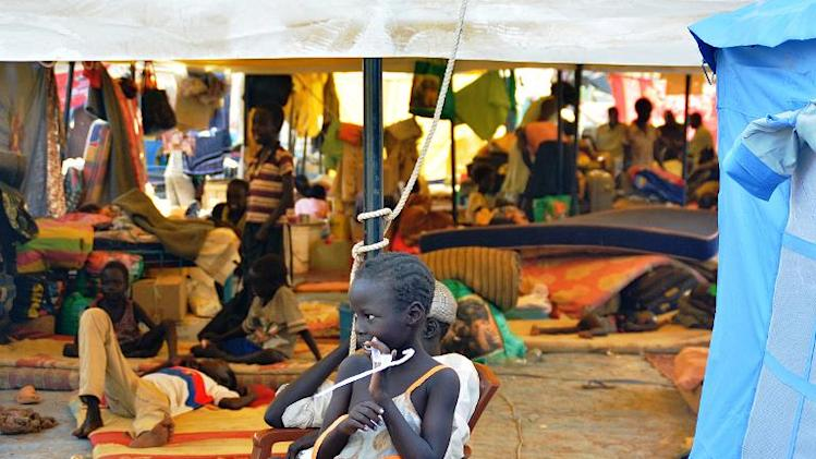 A South Sudanese child stands next to a tent crowded with IDP's at an encampment within the United Nations Mission in South Sudan, UNMISS compound on January 4, 2014 in the capital Juba