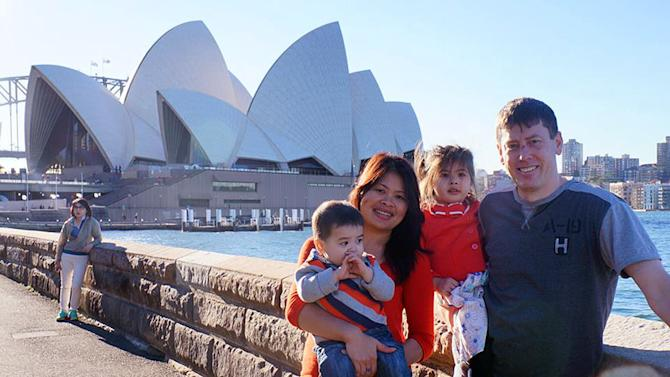 In this undated photo provided by the Rhodes family, Phoumalaysy Rhodes, second left, and her husband Gavin Rhodes, right, hold their children Manfred and Jadesuda, second right, near the Sydney Opera House in Sydney, Australia. The four are among 49 passengers and crew believed killed when a Lao Airlines plane crashed on Wednesday, Oct. 16, 2013, en route from the Lao capital Vientiane to Pakse in the Southeast Asian nation's south. (AP Photo/Rhodes Family)