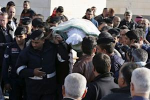 Police officers and relatives of Kamal Milkawi carry…