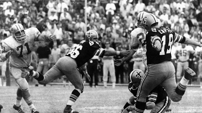 FILE - In this Nov. 8, 1970, file photo, New Orleans Saints' Tom Dempsey (19)  moves up to kick a 63-yard field goal as teammate Joe Scarpati holds the ball, Detroit Lions' Alex Karras (71) rushes in, and Saints' Bill Cody (66) blocks, in New Orleans. The record-setting kick, with 2 seconds left in the game, gave the Saints a 19-17 win. Karras is taking on the role of lead plaintiff: He and his wife, Susan Clark, are two of 119 people who filed suit Thursday, April 12, 2012, in U.S. District Court in Philadelphia, the latest complaint brought against the NFL by ex-players who say the league didn't do enough to protect them from head injuries. (AP Photo/Files)