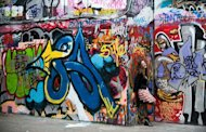 A woman poses to have her photograph taken in the graffiti and street art covered designated skate area on the South Bank in London on July 7, 2010. Far from London's beaten tourist track, a group of visitors is staring keenly at the graffiti-covered gates to an abandoned construction site