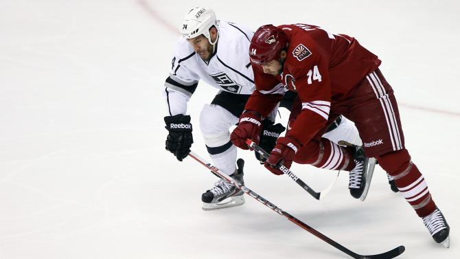 Phoenix Coyotes left wing Taylor Pyatt (14) and Los Angeles Kings left wing Dwight King (74) battle for the puck during the second period of Game 5 of the NHL hockey Stanley Cup Western Conference finals, Tuesday, May 22, 2012, in Glendale, Ariz. (AP Photo/Matt York)