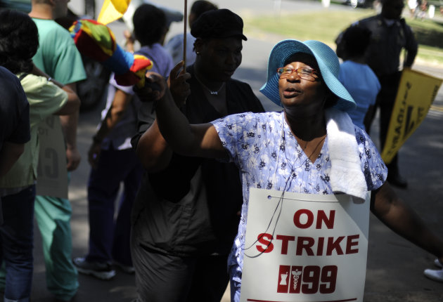 Nursing home worker Merlene Cooper gestures to a car crossing the picket line as she marches outside at Newington Health Care Center in Newington, Conn., Wednesday, July 11, 2012. Workers at five Heal