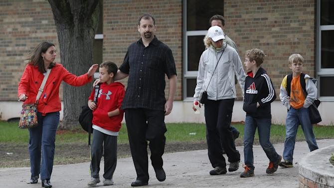 Parents and their children leave the Peter Hobart Elementary School in St. Louis Park, Minn., after a field trip to Lilydale Regional Park resulted in the death of at least one student Wednesday, May 22, 2013. A fourth-grade field trip to a Mississippi River park popular with fossil hunters turned deadly Wednesday when gravel saturated by persistent rain gave way. (AP Photo/The Star Tribune, Bruce Bisping)  MANDATORY CREDIT; ST. PAUL PIONEER PRESS OUT; MAGS OUT; TWIN CITIES TV OUT