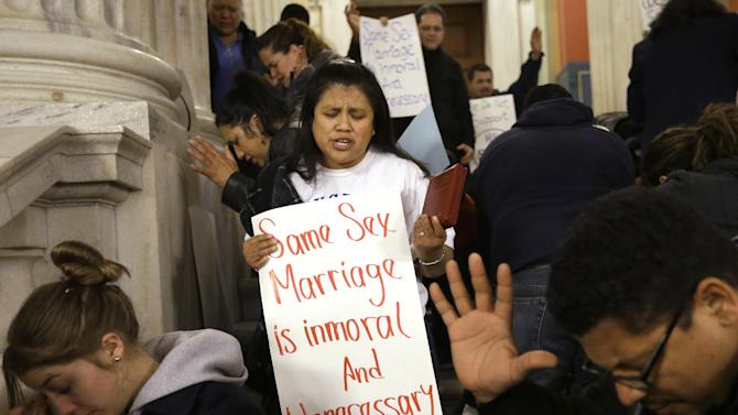Pascula Chamorro, of Providence, R.I., center, displays a placard as she joins with other demonstrators opposed to same-sex marriage as they pray during a rally at the Statehouse, in Providence, Tuesday, Jan. 15, 2013. The Rhode Island House Judiciary Committee began hearing testimony from supporters and opponents of same-sex marriage Tuesday. (AP Photo/Steven Senne)