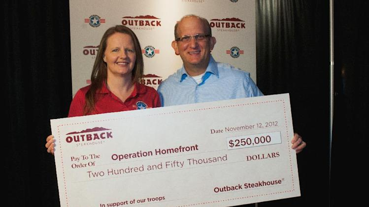 November 8, 2012, Chief Programs and Field Operations officer for Operation Homefront Amy Palmer (left) receives a $250,000 check from Outback Restaurant CMO Mike Kappitt (right). (Dean Dixon/AP Images for Outback)