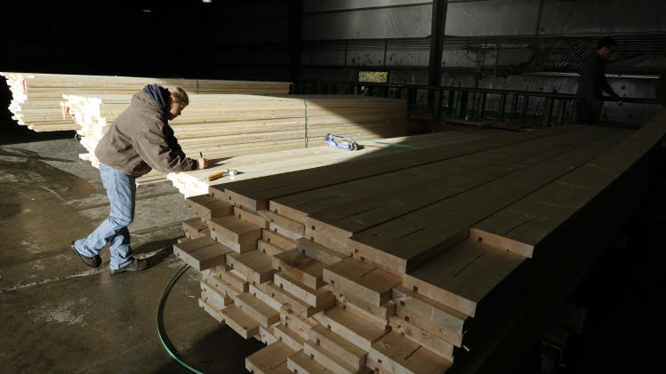 In this Friday, Dec. 21, 2012 photo, Erin Hall marks a load of wood trim at Belco Forest Products in Shelton, Wash. Hall was hired after an audit by the U.S. Immigration and Customs Enforcement Department resulted in the layoff of more than 20 workers for having suspect documents authorizing them to work in the United States. (AP Photo/Ted S. Warren)