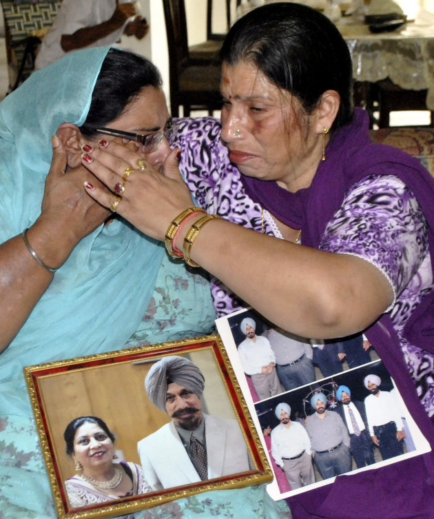 Harinder Kaur Rakhra, left, sister of Satwant Singh Kaleka who was killed in the shooting attack at a Sikh temple in the U.S. state of Wisconsin, is consoled by Seema Sharma, a local politician in Patiala, India, Monday, Aug. 6, 2012. Indian Prime Minister Manmohan Singh said Monday that he was shocked and saddened by the shooting attack that killed six people. The photo on left shows Satwant Singh Kaleka, with his wife Satpal Kaleka.
