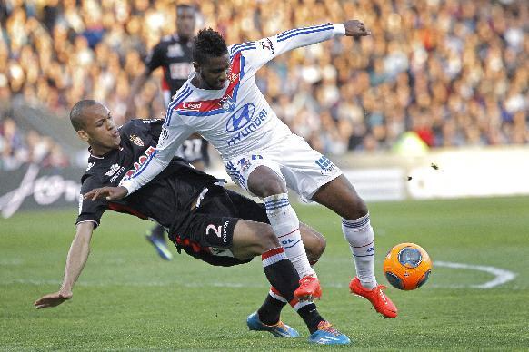 Lyon's Makengo Arnold Mvuemba, right, is tackled by Monaco's Fabio Henrique Tavares during their French League One soccer match in Lyon, central France, Sunday, March 16, 2014