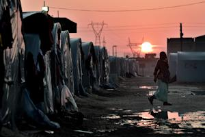 A Syrian Kurdish woman walks in a refugee camp in the…