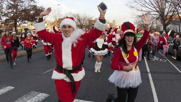 Participants in the Running of the Santas Festival run past the halfway mark before a rock music concert at The Electric Factory in Philadelphia, Pennsylvania