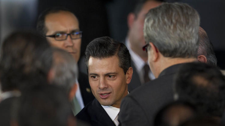 Mexico's President Enrique Pena Nieto, center, speaks to unidentified people after an event to announce an education reform proposal in Mexico City, Monday, Dec. 10, 2012. Pena Nieto is proposing sweeping reforms to the public education system widely seen as moribund, taking on Elba Esther Gordillo, an iron-fisted union leader who is considered the country's most powerful woman and the main obstacle to change. (AP Photo/Alexandre Meneghini)