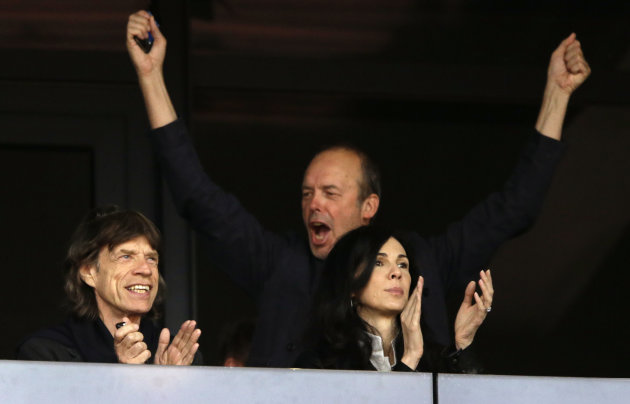 Musician Mick Jagger, left, watches an evening session of athletics competition with L&#39;Wren Scott, right, in the Olympic Stadium at the 2012 Summer Olympics, Monday, Aug. 6, 2012, in London. (AP Photo/Matt Slocum)