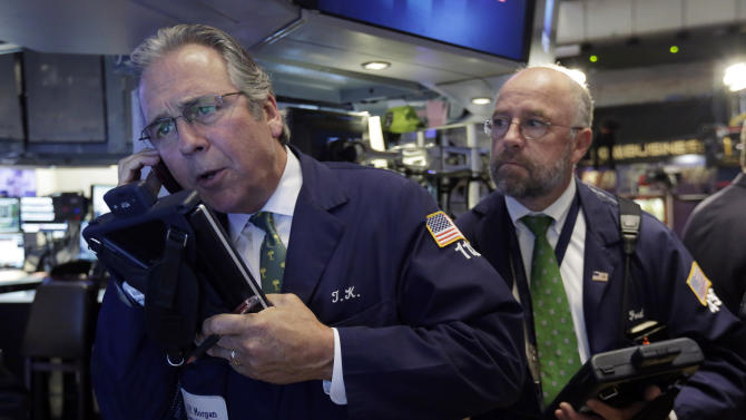 Traders Thomas Kay, left, and Frederick Reimer work on the floor of the New York Stock Exchange, Thursday, Aug. 7, 2014. U.S. stocks are opening slightly higher after Europe's main two central banks decided to keep interest rates on hold. (AP Photo/Richard Drew)