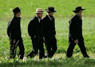Amish men walk to a funeral for a victim of the Amish schoolhouse shootings, on October 5, 2006, in Nickel Mines, Pennsylvania. The leader of a breakaway Amish group who ordered his followers to chop off his rivals' beards was sentenced Friday to 15 years in prison after being convicted of hate crimes.