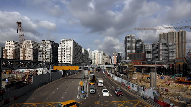 Cars travel down a road between blocks of 45-year-old residential flats and the latest luxury homes near the construction site for a high-speed railway, in West Kowloon, Hong Kong, China