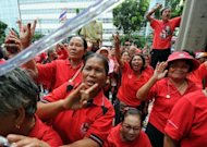 "Thai ""Red Shirt"" supporters shout sloagans during the terrorism trial of the group's leaders outside the Criminal Court in Bangkok. The terrorism trial of Thai ""Red Shirt"" leaders in connection with deadly civil unrest in 2010 has been postponed until November because some of the defendants enjoy immunity while parliament is in session"