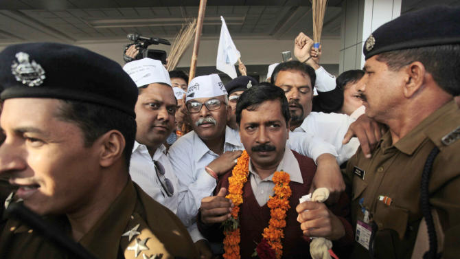Anti-graft activist and leader of Aam Aadmi Party, or Common Man Party, Arvind Kejriwal is surrounded by supporters after his arrival at the airport as he begins his four-day visit of Gujarat state ahead of the country's national elections, in Ahmadabad, India, Wednesday, March 5, 2014. India said Wednesday it will begin national elections on April 7, kicking off a month-long contest in the largest democracy in the world. More than 810 million people are eligible to vote this year, an increase of 100 million from five years ago, according to the Election Commission. (AP Photo/Ajit Solanki)